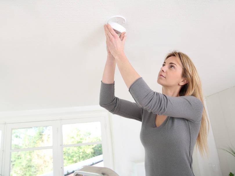 young-lady-testing-smoke-alarm